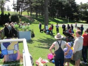 The crowd watches on as Ecopella sings round the garden beds